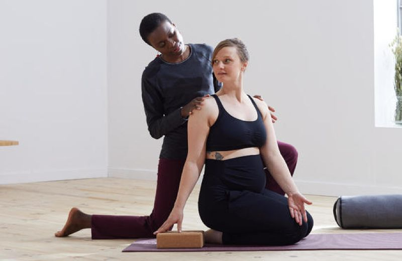 Mujer practicando yoga para embarazadas con profesora