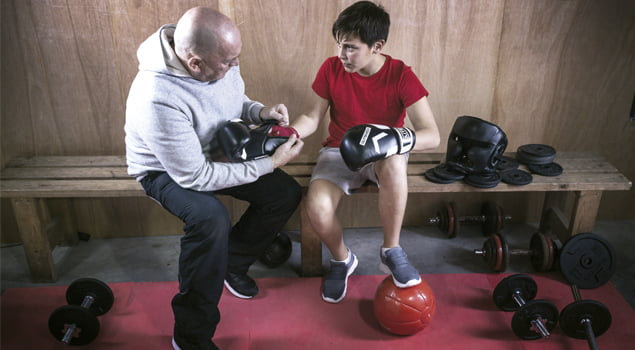 Entrenador poniendo los guantes de boxeo a su pupilo